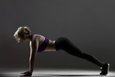 pushup: Beautiful sporty dancer girl in sportswear, warming up, doing push-ups, crossfit exercises for strong abs, shoulders, arms on black background, low key studio shot Stock Photo