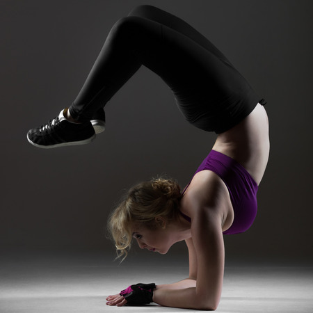 Beautiful dancer girl in sportswear warming up, doing backbend while standing on forearms, on black background, low key studio shot Stock Photo