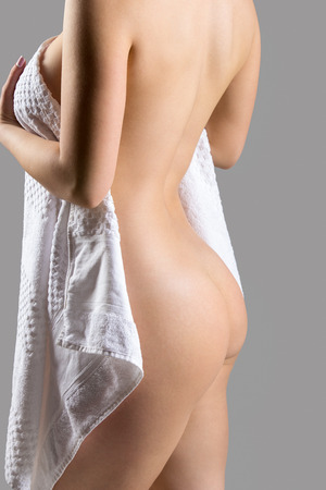 mujeres jovenes desnudas: Primer plano de irreconocible sexy hermosa mujer joven desnuda escondiéndose detrás de una toalla, la vista atrás, secándose después de conceptos de ducha, pérdida de peso, salud y cuidado de la piel
