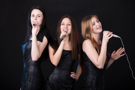 cantando: Grupo de tres emocionales hermosas cantantes jóvenes con micrófonos de canto, concierto de la banda niñas