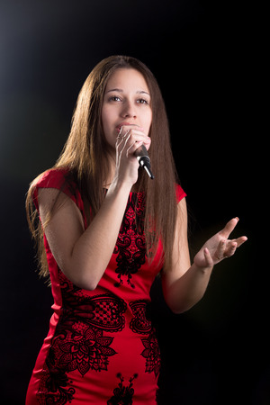 Portrait of beautiful girl in red dress passionately singing or acting with microphone