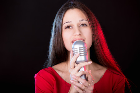 vocalist: Portrait of beautiful emotional girl vocalist in red dress singing holding silver vintage microphone