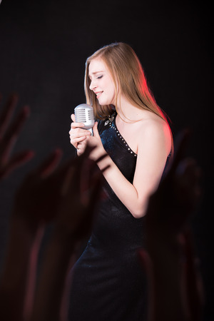 vocalist: Portrait of attractive vocalist girl singing with emotions holding silver vintage microphone, crowd of raised fans hands on foreground