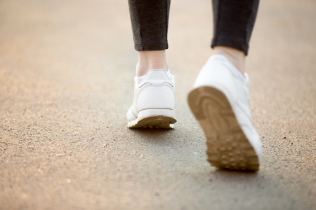 training shoes: Female feet in white sneakers running on concrete, jogger practicing, close-up. Healthy, active lifestyle concepts, copy space
