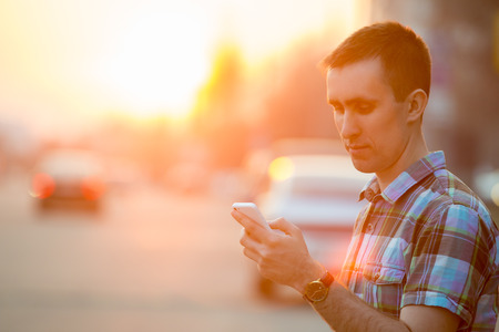mobile phone: Young man holding mobile phone, using smartphone app, scrolling, looking at screen, standing on sunny street with transport vehicles on the background