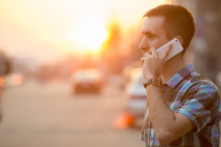 speaking: Young man holding mobile phone, using smartphone, making a call, talking on the phone, standing on sunny street with transport traffic on the background
