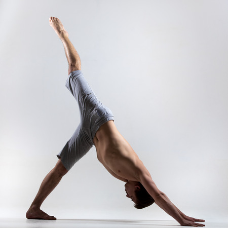 eka: Sporty young man working out, yoga, pilates, fitness training, standing in asana eka pada adho mukha svanasana, one legged downward facing dog pose
