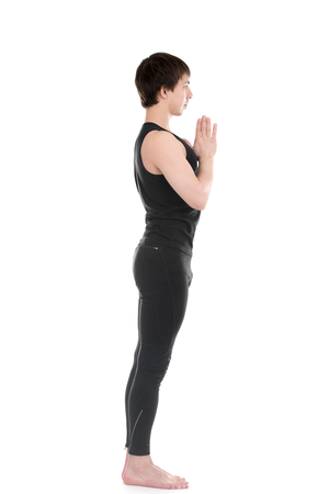 Profile of sporty young man practicing yoga, standing with hands joined in Namaste gesture, focusing, Anjali mudra, Pranamasana, for arms flexibility