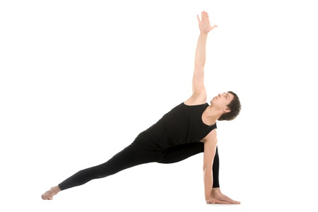 utthita: Sporty young man practicing yoga, doing stretching exercise, Extended Side Angle Pose, Utthita Parsvakonasana, therapeutic for low backache