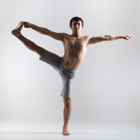 hasta: Sporty young man yoga, pilates, fitness practice, standing in yoga asana utthita hasta Padangustasana, extended hand to big toe pose (stretched hand grasps big toe), front view Stock Photo