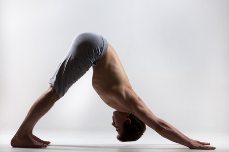 Profile of muscular handsome young man working out, standing in yoga downward facing dog pose, adho mukha svanasana, asana from Surya Namaskar sequence, Sun Salutation complex, low key shot