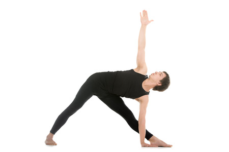 utthita: Sporty young man practicing yoga, doing stretching exercise, extended triangle pose, utthita trikonasana asana for flexible spine and relieving stress
