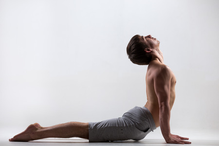 Profile of sporty muscular young man working out, yoga, pilates, fitness training, exercises for flexible spine, urdhva mukha shvanasana, upward facing dog pose, gray background, low key shot