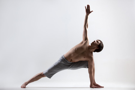 revolved: Sporty muscular young man working out, yoga, pilates, fitness training doing lunge exercise, Revolved Side Angle Pose, Parivrtta Parsvakonasana, gray background, low key shot Stock Photo