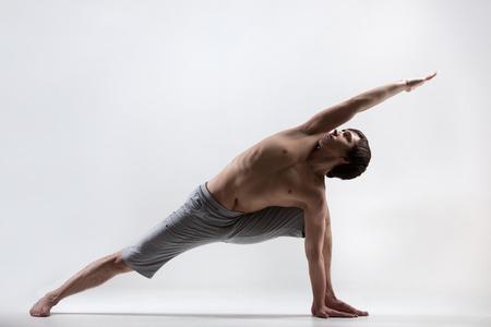 Sporty muscular young man working out, yoga, pilates, fitness training doing lunge exercise, Utthita Parsva Konasana (Extended Side Angle Pose), gray background, low key shot photo
