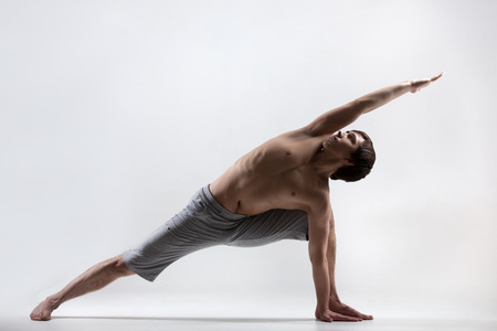 side angle pose: Sporty muscular young man working out, yoga, pilates, fitness training doing lunge exercise, Utthita Parsva Konasana (Extended Side Angle Pose), gray background, low key shot