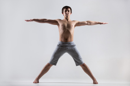 utthita: Sporty young man working out, yoga, pilates, fitness training, standing in Utthita Tadasana, Five Pointed Star Pose, energizing, basic posture Stock Photo