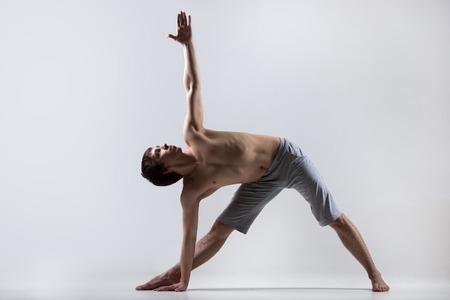 trikonasana: Sporty muscular young man working out, yoga, pilates, fitness training, Triangle pose, Trikonasana, stretching exercise, gray background, low key shot
