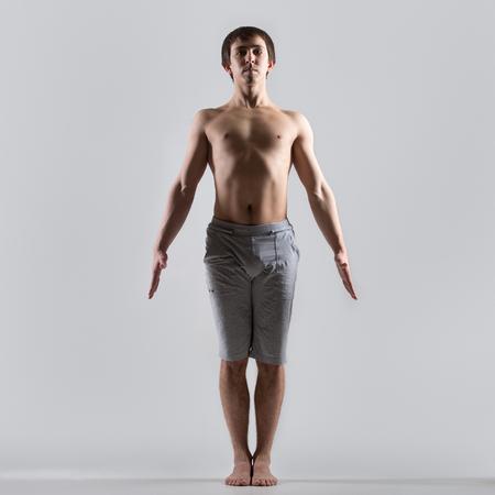 namaskar: Sporty muscular young man working out, yoga, pilates, fitness training, basic standing asana tadasana, mountain yoga posture, pose from surya namaskar, gray background, low key shot