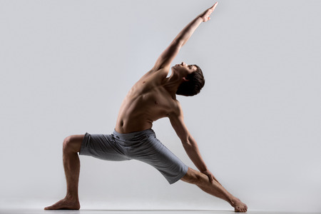 Sporty muscular young man working out, yoga, pilates, fitness training, high lunge exercise, Reverse Warrior Pose, Crescent variation, Viparita Virabhadrasana, gray background, low key shot 스톡 콘텐츠