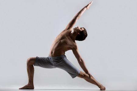 Sportieve, gespierde jonge man uit te werken, yoga, pilates, fitness, hoge lunge oefening, Reverse Warrior Pose, Crescent variatie Viparita Virabhadrasana, grijze achtergrond, low key schot