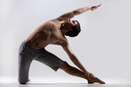 pilates studio: Athletic muscular young man working out, yoga, pilates, fitness training, doing side bend, asana Parighasana, Gate Yoga Pose, gray background, low key shot Stock Photo