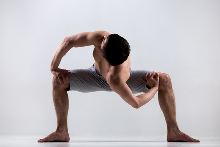 pilates studio: Athletic muscular young man working out, yoga, pilates, fitness training, doing sumo squat exercises, revolved temple, goddess, sumo wrestler pose