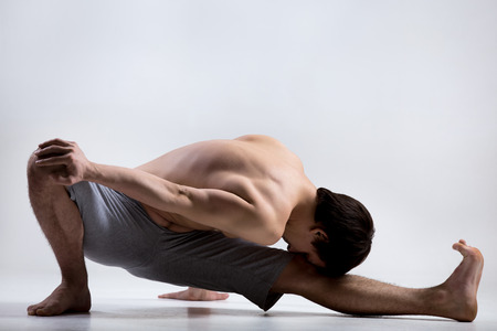 reducing: Athletic muscular young man working out, yoga, pilates, fitness training, sitting, bending forward in Marichyasana I, pose dedicated to the Sage Marichi I, exercise reducing weight