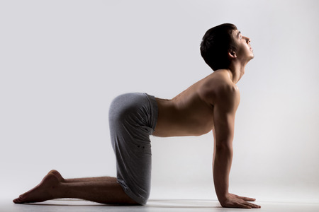 exhale: Sporty muscular young man working out, yoga, pilates, fitness training, bend in Cow yoga posture, Bitilasana, asana often paired with Cat Pose on the exhale, gray background, low key shot Stock Photo