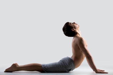 bhujangasana: Profile of sporty young man working out, doing exercises for flexible spine, bhudjangasana (Bhujangasana or Cobra Pose), gray background, low key shot