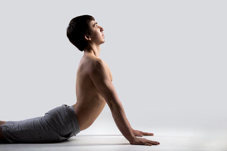 bhujangasana: Profile of sporty young man working out, doing exercises for flexible spine, bhudjangasana (Bhujangasana or Cobra Pose), gray background, low key shot, close-up