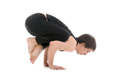 crow: Sporty young man working out, doing handstand yoga asana, Crane (Crow) Pose with crossed legs, Bakasana for shoulders, upper back, arms and wrists