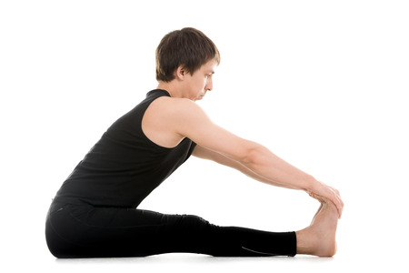 Athletic young man does yoga, pilates or fitness exercises, seated Forward Bend pose (Intense Dorsal Stretch), Paschimottanasana, stretching spine, shoulders, hamstrings photo