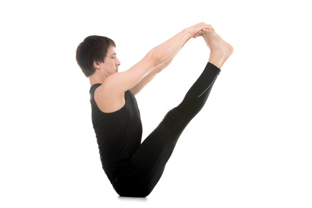 pilates man: Sporty young man doing yoga or pilates exercises, sitting in Ubhaya Padangusthasana, Both Feet Big Toe, Double toe hold, V pose, Balancing Stick Pose