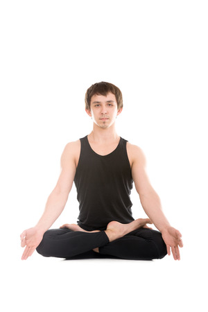 mudra: Meditation, sporty serene young man sitting in cross-legged yoga lotus pose, Padmasana with fingers in yogic gesture Chin Mudra Stock Photo