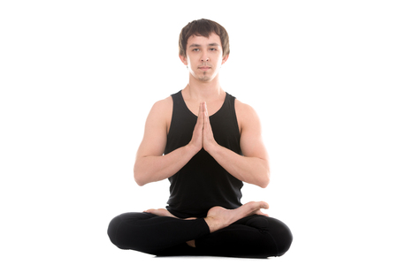 Sporty serene young man meditating sitting in cross-legged yoga lotus pose, Padmasana with palms in Namaste