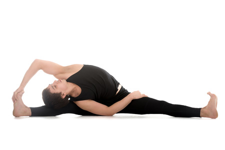revolved: Athletic young man doing yoga, pilates, stretching practice, sitting in splits, Parivrtta Upavistha Konasana, Revolved Seated Angle Pose