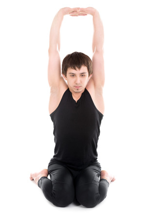 pilates studio: Sporty young man working out, yoga, pilates, fitness training, siting in virasana, hero pose, stretching clasped hands
