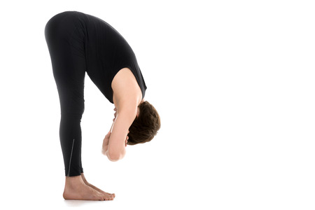 Profile of sporty young man on white background in uttanasana with elbow grab (intense stretch pose, forward bend, forward fold, head to knees), surya namaskar, sun salutation complex