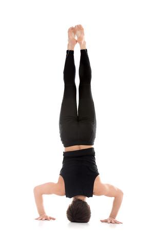 headstand: Sporty young man working out, yoga, pilates, fitness training, doing Tripod Headstand, Salamba Sirsasana II, back view