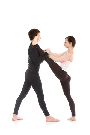 hasta: Two sporty people practice yoga in pair, girl doing stretching exercise, Extended Hand to Big Toe yoga pose, Utthita Hasta Padangushthasana with partner or coach assistance Stock Photo