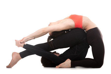 ushtrasana: Sporty couple on white background doing acroyoga, fitness or pilates practice in pair, yoga with partner, Camel (ustrasana) with Plow (halasana) Pose