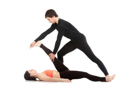 big toe: Two sporty people practicing yoga with partner, young male coach helping girl to do reclining hand to big toe pose, supta padangusthasana