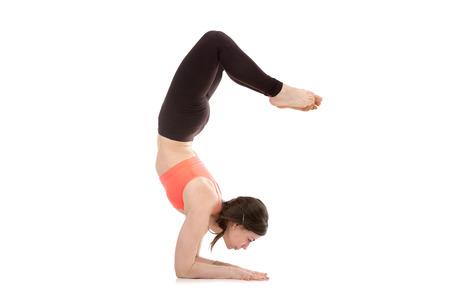 Profile of sporty yogi girl doing fitness exercises, yoga asana Scorpion Pose Vrischikasana 1 posture, forearm stand, inverted backbend pose photo