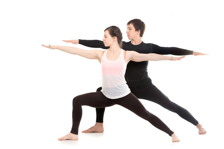 Two sporty people practice yoga with partner, doing lunge exercise, Warrior II posture, Virabhadrasana 2, side view