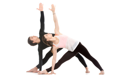 Two sporty people practice yoga with partner, couple doing stretching exercise, extended triangle pose, utthita trikonasana Stock Photo