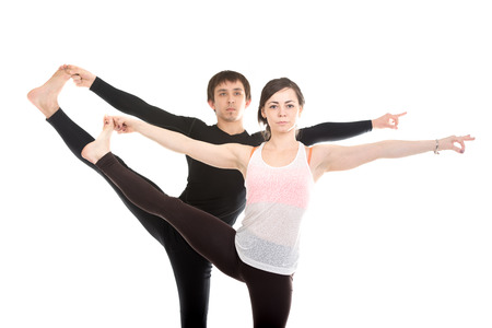 big toe: Two sporty people practice yoga with partner, couple doing stretching exercise, Extended Hand to Big Toe yoga pose, Utthita Hasta Padangushthasana, close-up