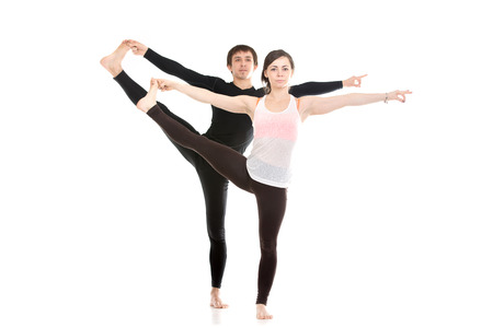 hasta: Two sporty people practice yoga with partner, couple doing stretching exercise, Extended Hand to Big Toe yoga pose, Utthita Hasta Padangushthasana, full length Stock Photo