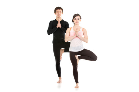 Two sporty people practice yoga in pair, couple doing exercise for spine, standing in Tree Pose, hands in Namaste, Anjali mudra Stock Photo