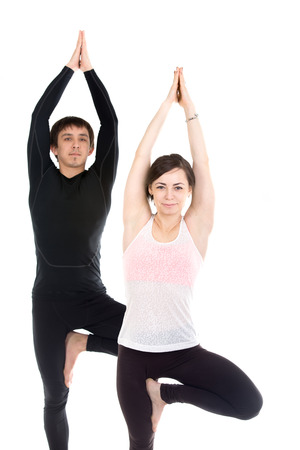 Two smiling sporty people practice yoga in pair, couple doing exercise for spine, standing in Tree Pose, hands above the head in Anjali mudra
